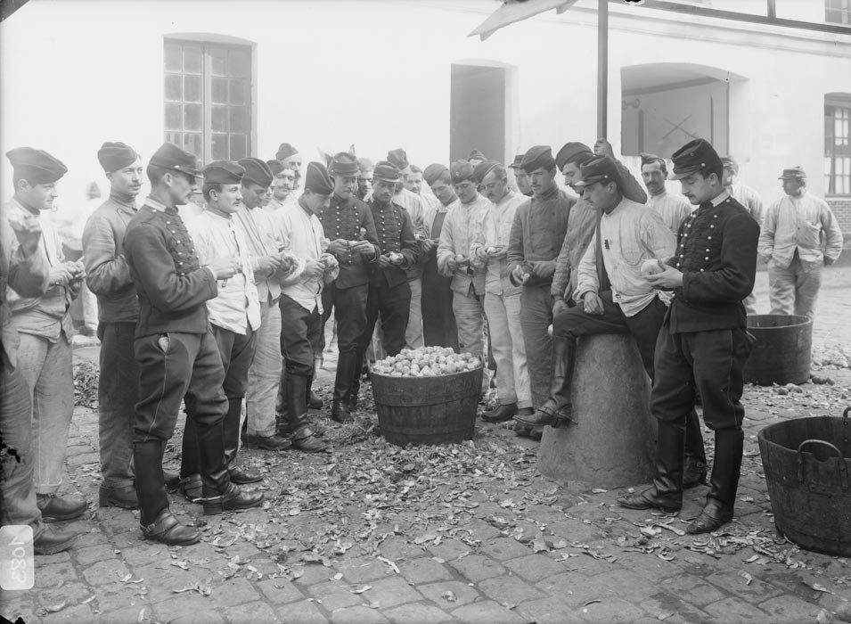 Les cavaliers d'un regiment de dragons preposés a la corvee d'epluchage de pommes de terre.