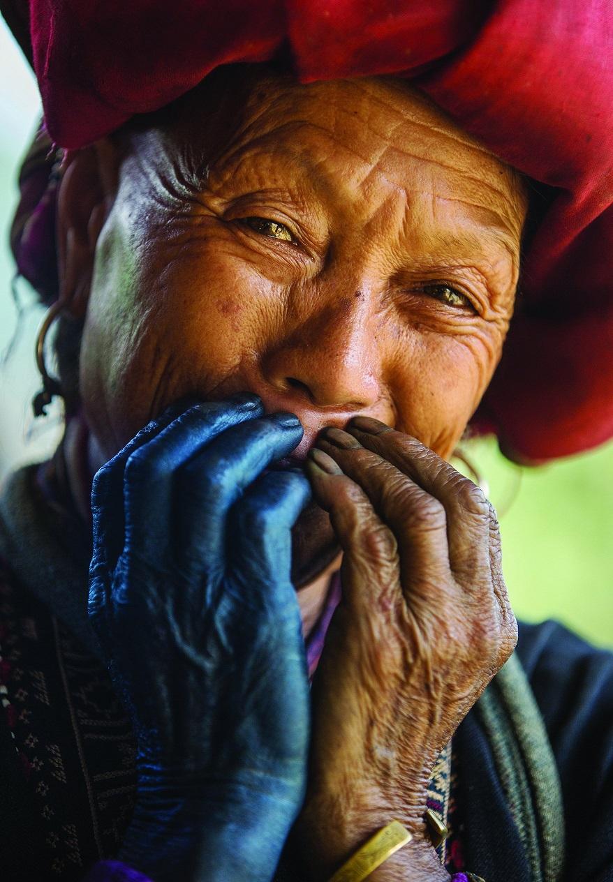 Женщина племени дао — в красной шляпе, с крашенной индиго рукой — она делала традиционный костюм.