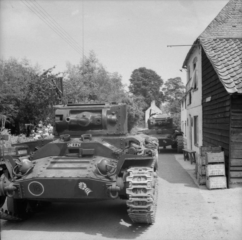 "Valentine tanks of 6th Armoured Division passing through a village during exercises in Bedfordshire, 25 July 1941. The leading vehicle is named ""Sneezy""."