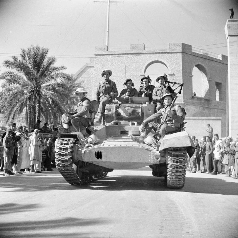 A piper of the Gordon Highlanders plays from a Valentine tank as it drives into Tripoli past crowds of cheering locals, 26 January 1943.