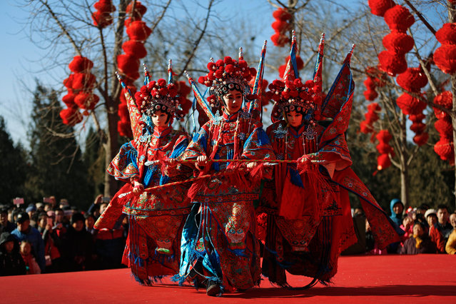A Chinese dancer dressed in traditional costume performs a cultural dance on stage during a temple f