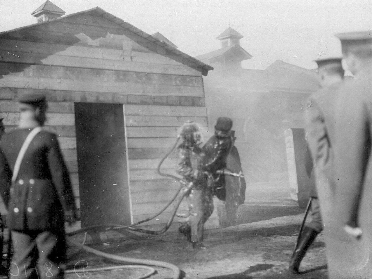 12. Великая княгиня Мария Павловна и сопровождающие ее лица наблюдают за работой пожарных в противодымном скафандре