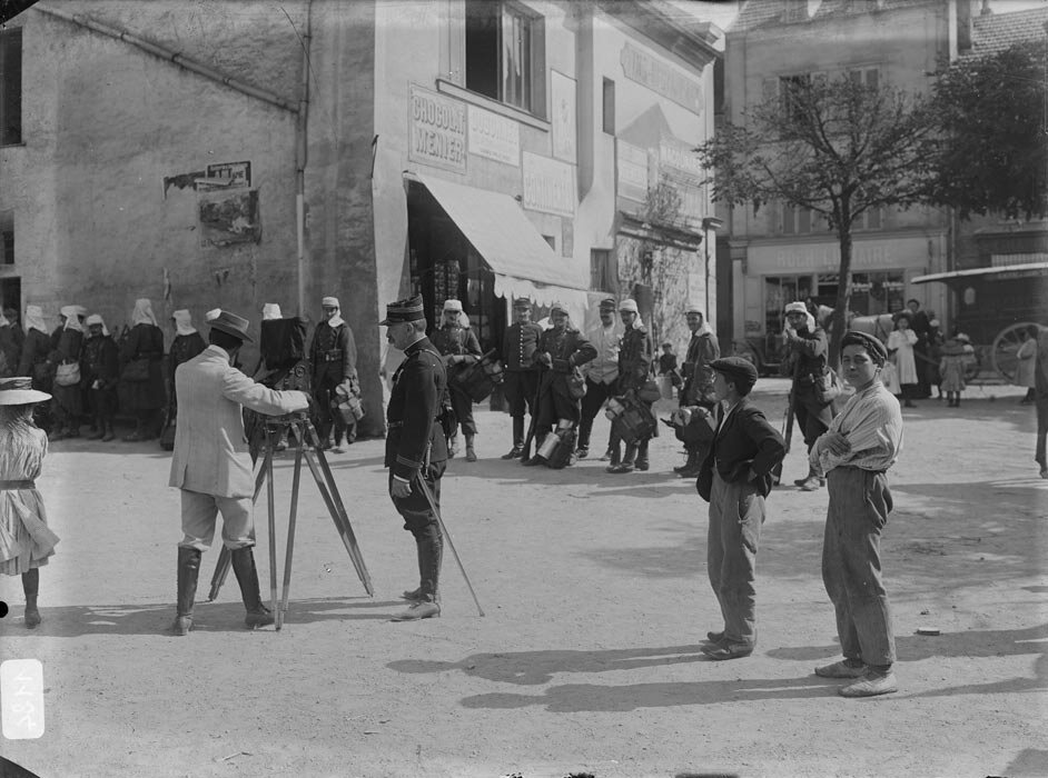 Un photographe realise une prise de vue d'une file de militaires de passage dans un village sous les yeux curieux des passants.