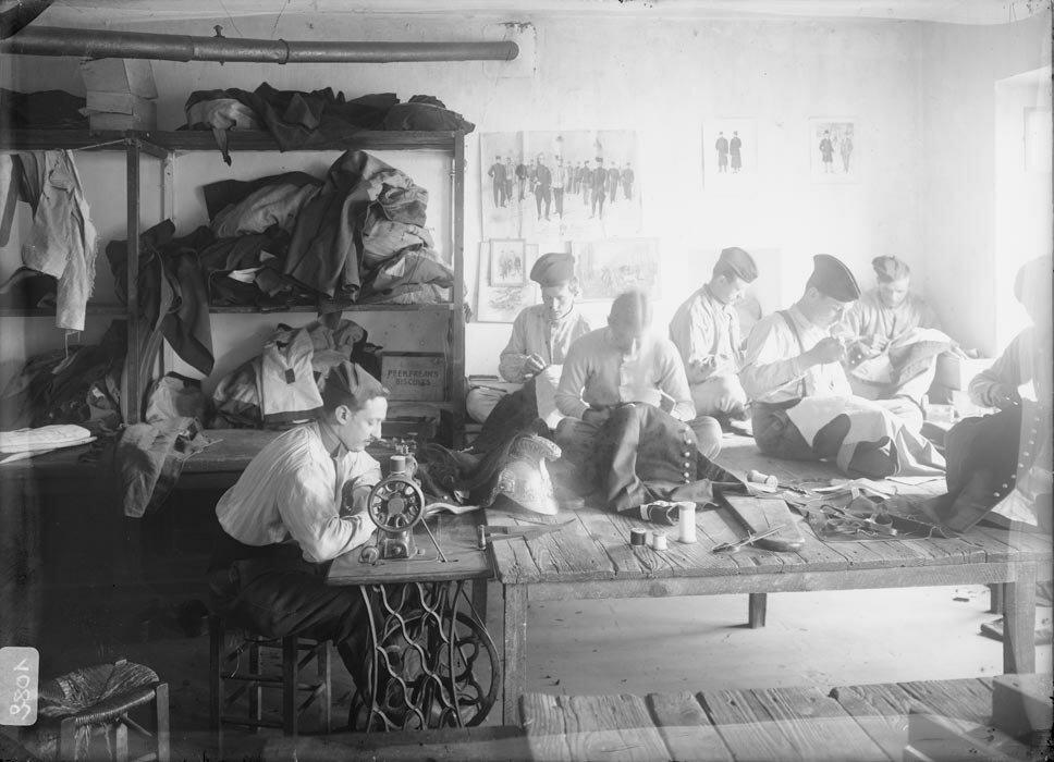 Les cavaliers d'un regiment de dragons en tenue de cantonnement raccommodent les uniformes.