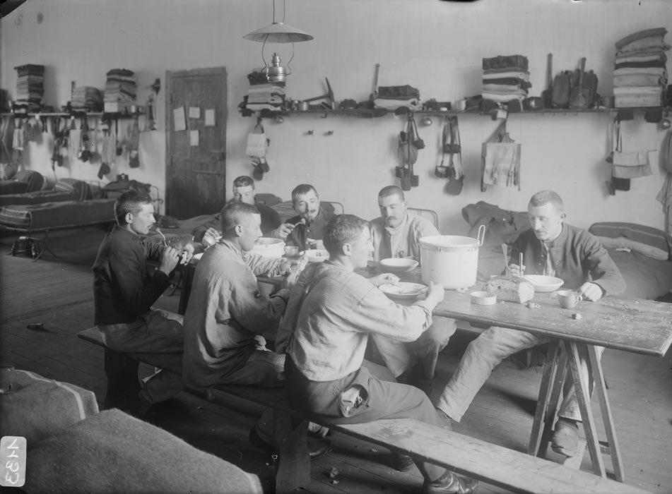 Un groupe de soldats du 89e regiment d'infanterie mange sa soupe dans une chambree.