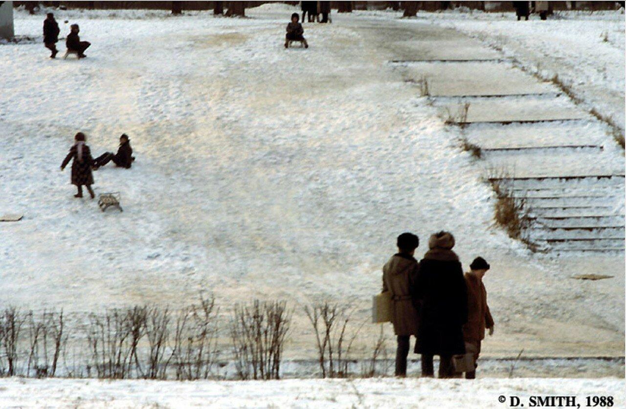 Дети катаются на санках вниз по склону холма