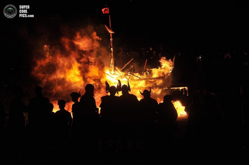 Силуэты шетландцев на фоне догорающего судна. (ANDY BUCHANAN/AFP/Getty Images)