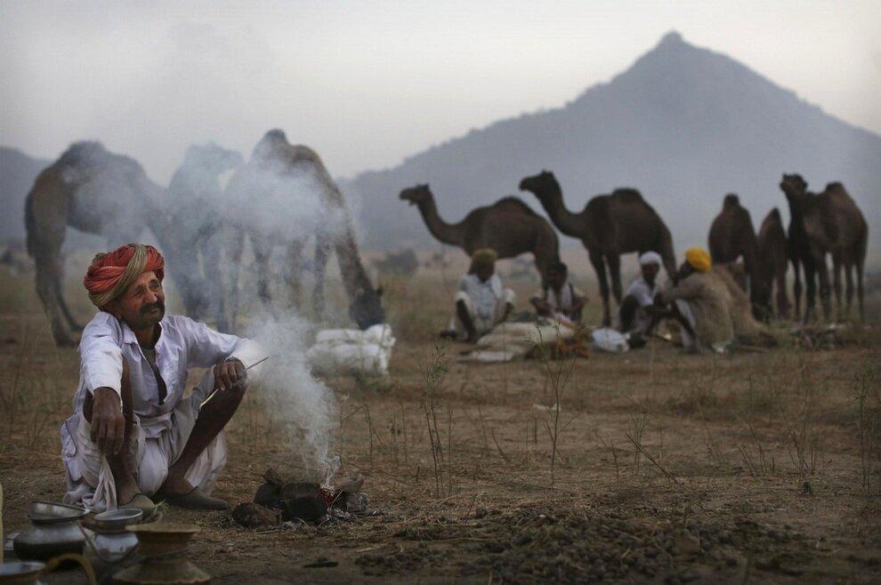 Индийский торговец разжигает небольшой костер в ожидании клиентов.
