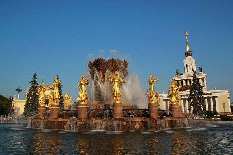 Золотые фигуры фонтана Дружбы народов СССР (Золотой сноп) и главный павильон на ВДНХ