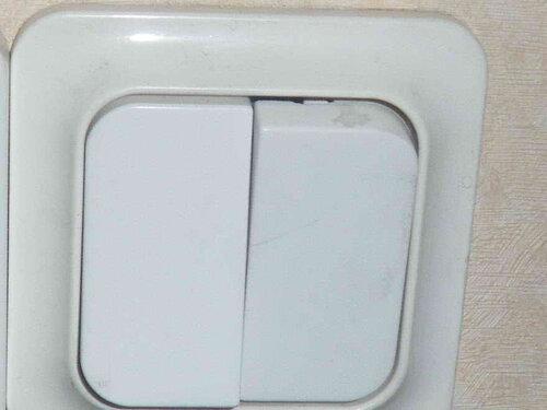 Фото 22. Двухклавишный выключатель «Элио тренд» («Eljo trend»). Крупный план. Правая клавиша пострадала от неквалифицированных действий какого-то «электрика». На клавише видна трещина (посередине) и скол пластмассы (в верхней части).
