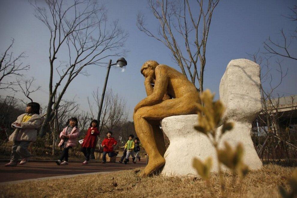 Дети рассматривают скульптуру «Мыслитель на унитазе» в Парке туалетной культуры, Сувон, провинция Кёнгидо, Южная Корея.