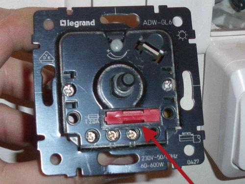 Фото 5. Корпус диммера «Легран» («Legrand»). Крупный план. Тёмно-красной стрелкой указан держатель предохранителя диммера (номинал предохранителя - 2 А).