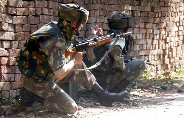 Indian army soldiers take position during a gunbattle.