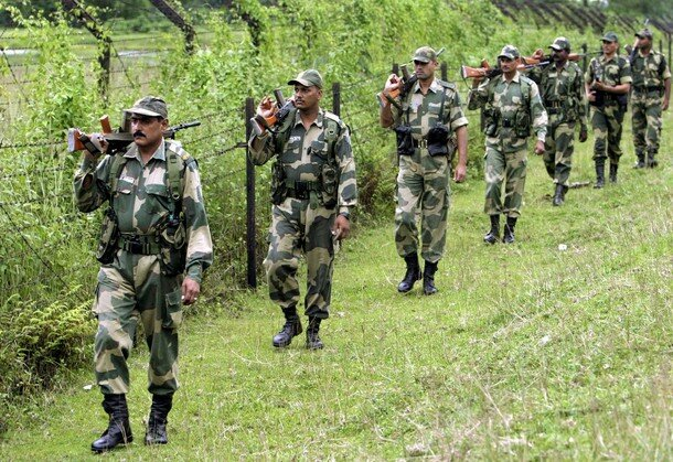 Indian BSF soldiers patrol along the fenced border with Bangladesh ahead of India's Independence Day celebrations in Fulbari village
