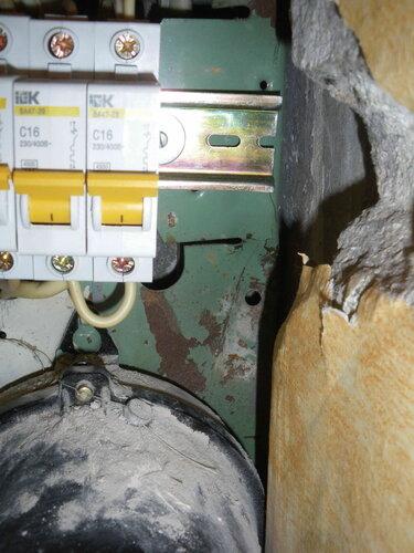 Фото 7. DIN-рейка зафиксирована винтами, установленными на месте крепления пакетного выключателя. Деформация корпуса щита не позволяет установить DIN-рейку строго горизонтально.