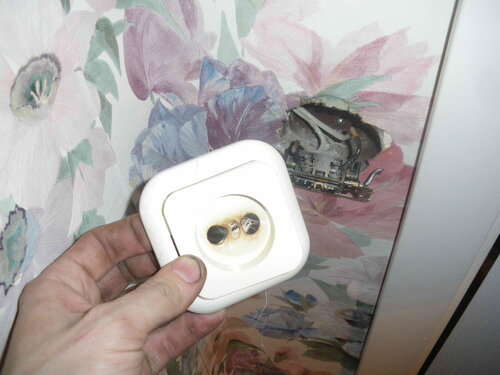 Фото 1. Демонтаж оплавленной крышки неисправной розетки. Розетка вырвана из установочной коробки.