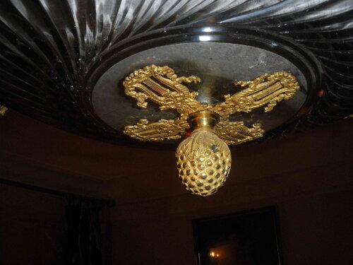 Фото 2. Декоративная шишка люстры. Основание шишки выполнено в виде четырёх направленных в разные стороны лир.