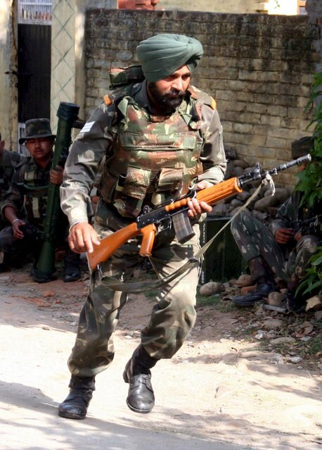 An Indian army soldier runs to take position during a gunbattle.