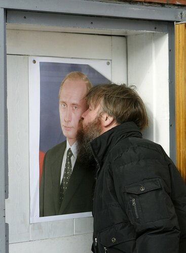A man kisses a portrait of Russia's Prime Minister Vladimir Putin at the entrance of his garage in Russia's Siberian city of Krasnoyarsk