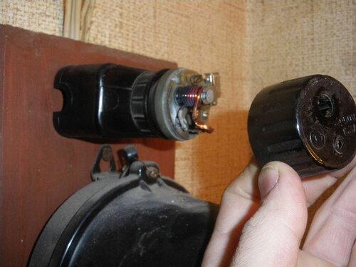 Фото 2. Предохранитель автоматический резьбовой (ПАР) развалился на несколько частей. В руке электрика верхняя часть корпуса ПАР.