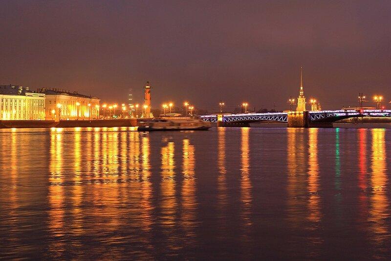 Ночной вид на Дворцовый мост, Университетскую набережную, ростральные колонны и шпиль Петропавловской крепости. Отражение огней фонарей в вечерней Неве.