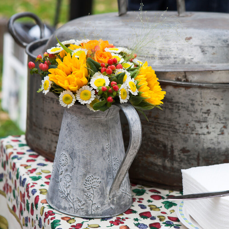 autumn flowers in an aluminum pitcher as table decoration on colored tablecloths