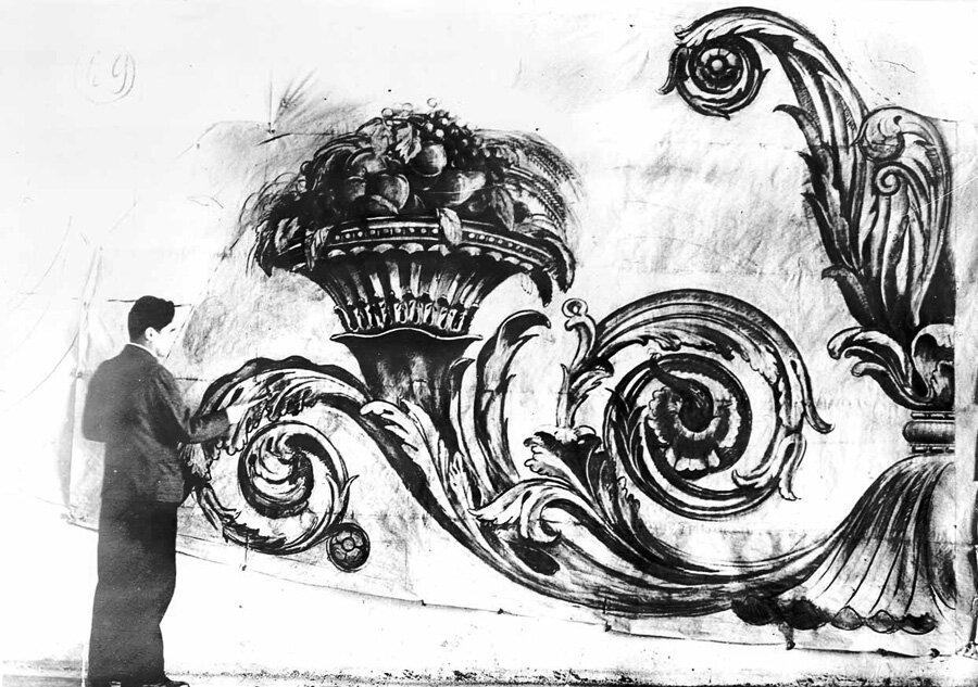 Художник за разработкой картины для росписи зрительного зала