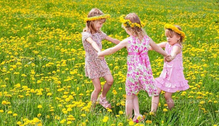Children playing on a dandelion field
