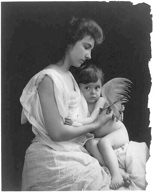 Woman holding scissors and winged child.