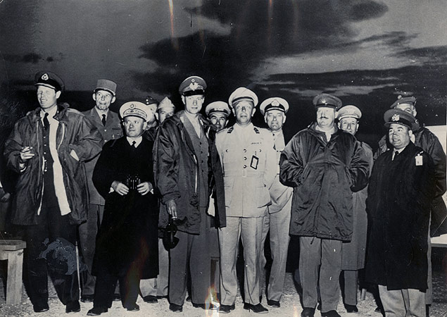 Eight official observers from NATO member countries are pictured against the dispersing clouds of an early morning atomic bomb test in Nevada