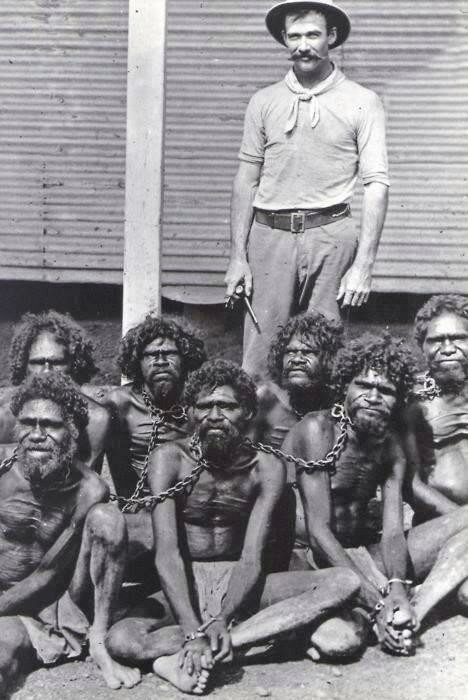 Australian man stands with his new Aboriginals captives. 1910s.jpg