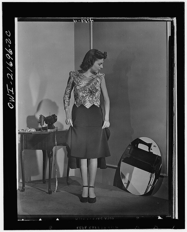 Dress almost finished, Cynthia adjusts her skirt length 1943.