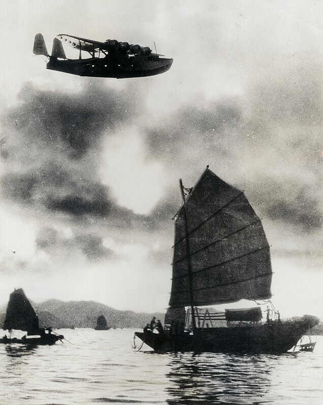 Pan Am's China Clipper soars over an old Chinese junk near Hong Kong Harbor