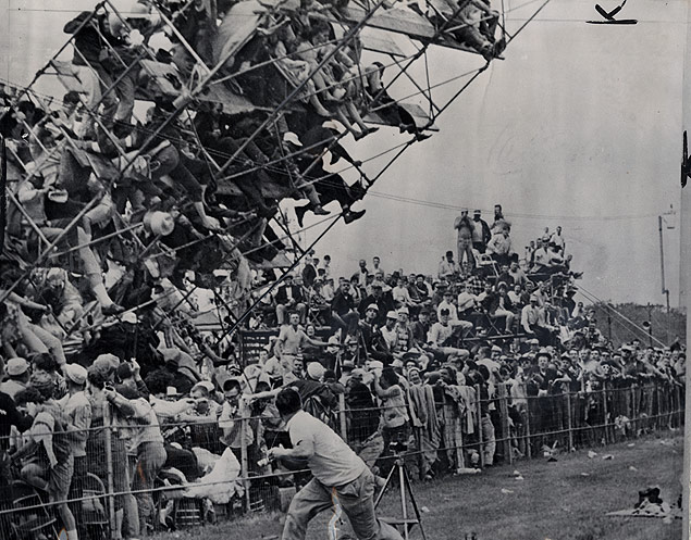 Fans on the ground and atop a 30-foot aluminum tower scramble as it begins to collapse before the start of the Indianapolis 500 race