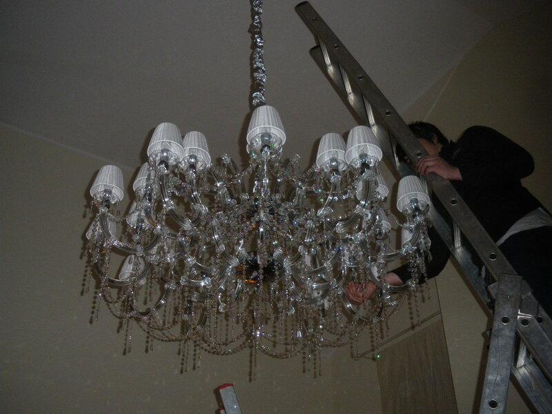 Фото 2. Установка крупной люстры в коттедже. Установка абажуров на клипсу - абажуры прикрепляются  к колбам ламп накаливания в форме свечей.