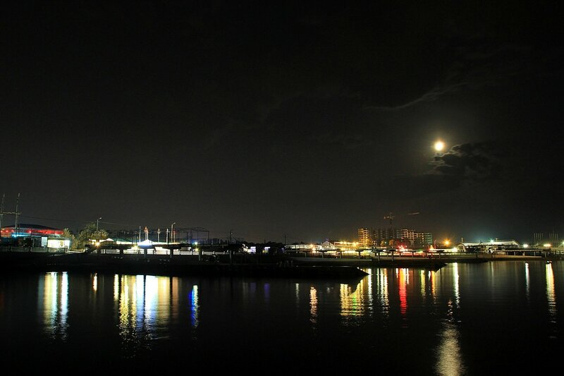 Ночные огни Севастополя и луна с облаками. Вид с моря, с волнореза на пляже парка Победы.