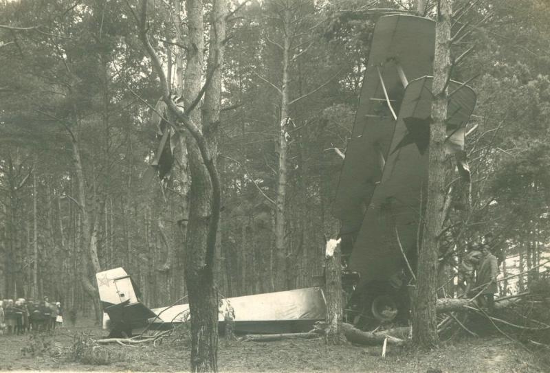 Среди деревьев в лесу упавший самолет-биплан с пятиконечной звездой на крыле и хвосте. Слева стоит группа людей. 1920-е.jpg