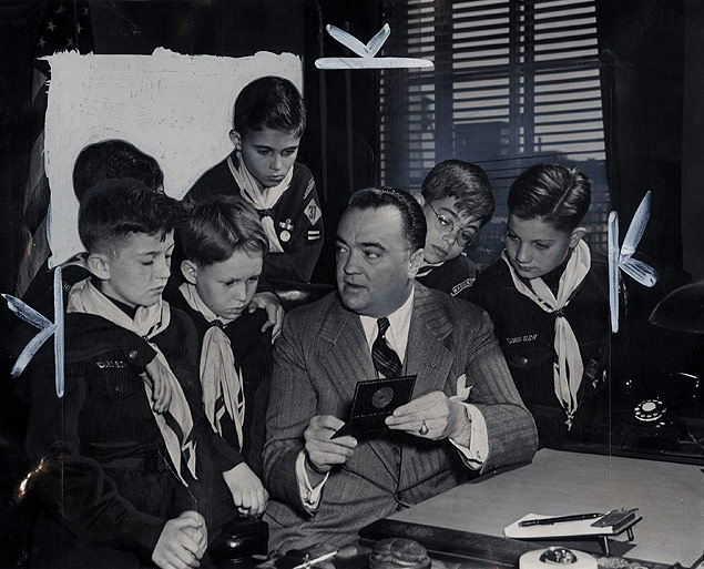 Director J. Edgar Hoover, displays his credentials to a troop of Cub Scouts at the start of theri tour of FBI Headquarters in Washington, D.C.