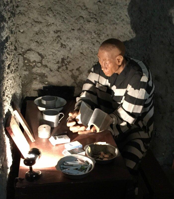 Восковая фигура заключенного, читающего Библию