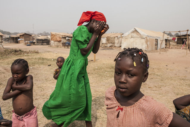 A young girl covers her face in laughter outside a church in the M'Poko Internally Displaced Pe
