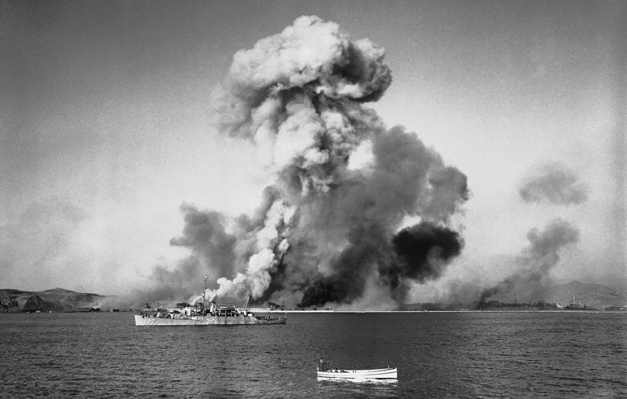 A large column of smoke mushrooms skyward as supplies and military installations are dynamited at Hu