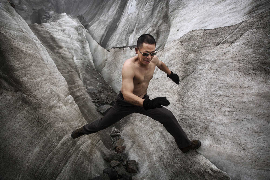 A shirtless Chinese tourist walks in the tongue of Glacier 1 at the base of the 7,556 meter (24,790