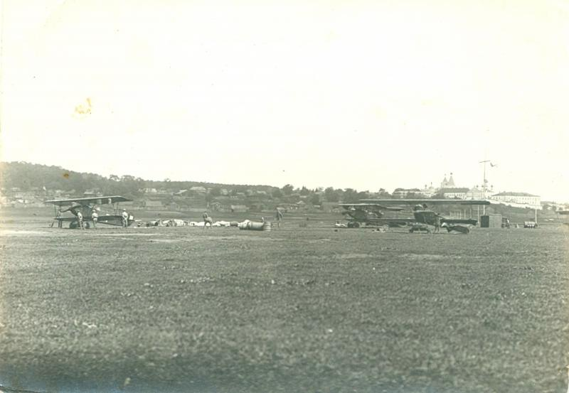 На аэродроме стоят три самолета; справа на линии горизонта монастырские постройки. 1920-е.jpg