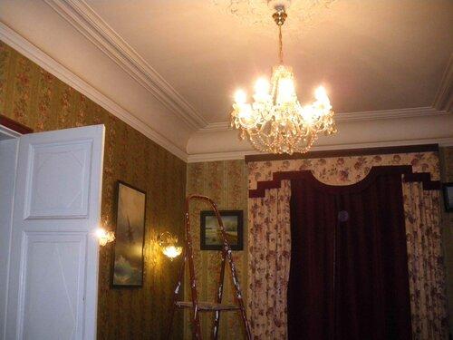 Фото 3. Современная хрустальная люстра классического дизайна. Бра на стене (2 штуки) составляют единый ансамбль с люстрой. Лампы накаливания излучают приятный тёплый свет.