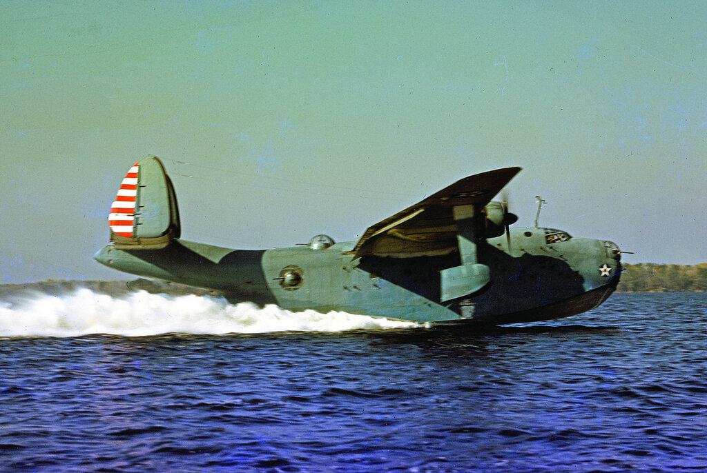 Left side view of early-model U. S. Navy Martin PBM Mariner taking off with paratroopers on board, 1943.