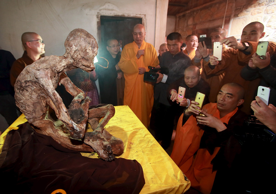 Monks take pictures with their mobile phones of the mummified body of a monk at Puzhao temple in Qua