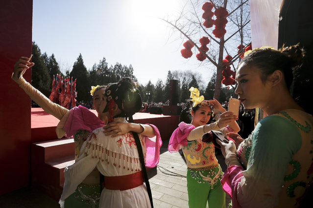 Chinese dancers dressed in traditional costume take selfies in backstage during a temple fair for a