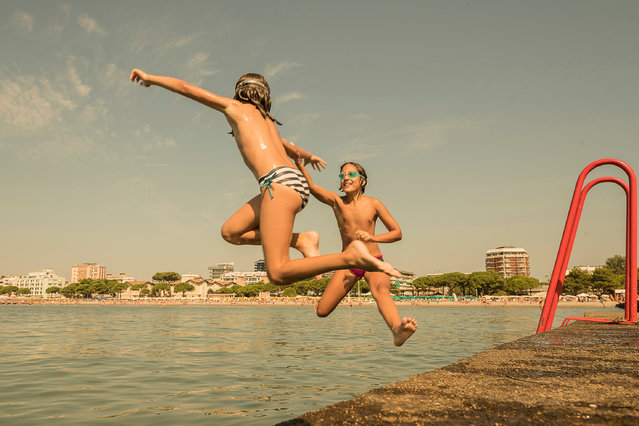 Andrea Rossato, Italy. Professional; Candid. Children enjoy the simple pleasures of a seaside holida