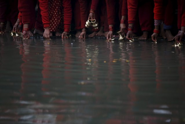 Devotees fill their vessels with water, which is considered by them to be holy, from the Bagmati Riv