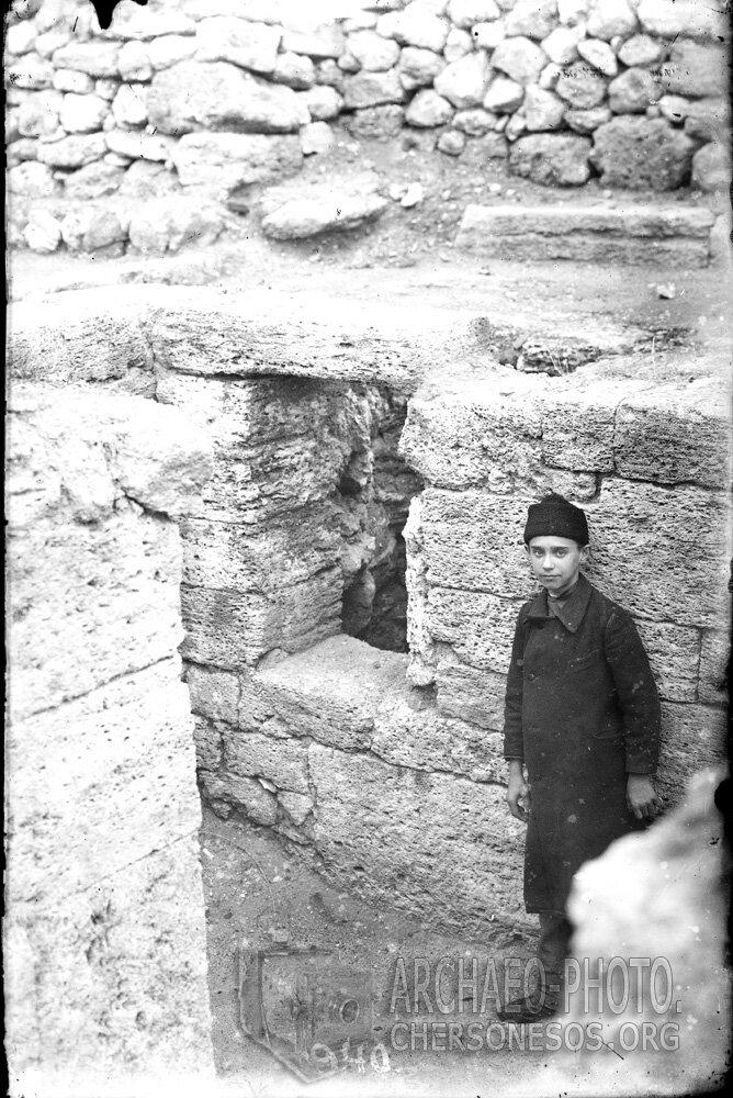 Мальчик в раскопанном помещении т.н. Монетного двора. 1904 год
